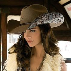 CUT ABOVE by CHARLIE 1 HORSE! A pecan wool cowgirl hat, features a deep crease sloped crown. Elegantly made with hand-tooled leather cut outs under the 4 brim with matching band. Finished off with a front brand of the CHARLIE 1 HORSE logo.