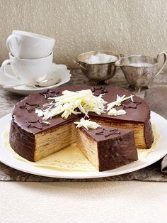 Baumkuchen-Torte Zutaten (16 Stücke)  9 Eier, 375 g Butter, 375 g Zucker, 1 Päckchen Vanillin-Zucker, 3-4 EL Rum, 150 g Speisestärke, 1 Päckchen Backpulver, 225 g Mehl, 200 g Orangenmarmelade, 300 g Zartbitter-Kuvertüre, 20 g Kokosfett, 50 g weiße Kuvertüre, Schokoladensterne zum Verzieren, Backpapier
