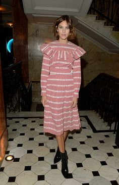 Alexa Chung wears a red and white Miu Miu dress with ruffle detailing and black boots