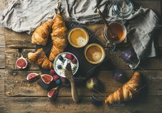 #Breakfast with croissants  Breakfast with croissants homemade ricotta cheese figs fresh berries honey and espresso coffee on dark serving board over rustic wooden background top view horizontal composition