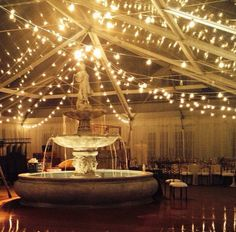 Wedding under a bistro light clear top tent at Trump Grand Hall. Water fountain in Terrace.