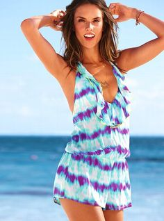 Boho beauty. This one piece cover-up goes electric in a 70's inspired tie-dye print. Neon-piped ruffles play along the plunging halter neckline (perfect for showing sunkissed skin). The cinched waist and short and sweet length make this chic little romper perfect from sea to sidewalk. Beachy, bright and right on trend, from our Beach Sexy® Collection.