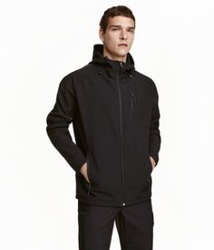 Black. Softshell jacket in windproof functional fabric with a hood with an elastic drawstring and small peak, a zip at the front and zipped side pockets.