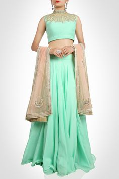 Pastels are ruling this season. Look dapper in this mint green lehenga, perfect for summer weddings. Enhancing the look is the ornate neckline encrusted with kundan and zari work. The beige dupatta lined with pearls and sequin motifs adds appeal
