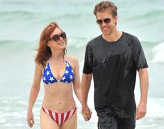 Kathy Griffin flaunts her taut tummy -- and her much younger new man --while wearing a star-spangled bikini on the beach in Miami on June 1, 2012.