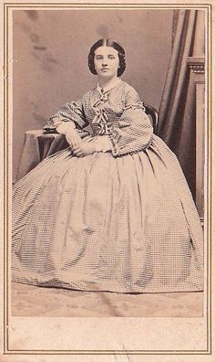 Very small check. High bodice, shaped sleeves demi open, pleated skirt. Ribbon trimmed armscyes and sleeve openings; 3 ribbon bows descending bodice. Shown with collar, jewelry.