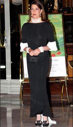 Carolina con un elegante vestido negro y gargantilla, pulseras y pendientes de perlas.