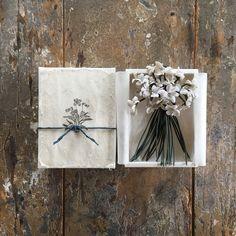 てづくり一点ものコサージュ。suMire-bouquetのお花たちをご覧いただきありがとうございます。私は一人工房で製作しています。布で作られたお花、布花です。白い布を花びらの形に切り、ひとつひとつ手染めして、コテをあて形成し、丁寧に仕上げました。プロフィールもあわせてお読みくださいませ。全長約17センチメートル。しろいスミレをガサッと束ねたコサージュにしたてました。爽やかな花束に茎は、斜茎を使用。斜茎とは特殊なコテで布をストロー状にする技法です。アンティークの布花にもつかわれています。シリアス染料で色を調合し手染めしています。布でできているため繊細です。水分、圧力にご注意ください。潰してしまうと元に戻らなくなります。水分や摩擦により色落ちしたり変色する事があります。十分にご注意くださいませ。箱にお入れして発送いたします。