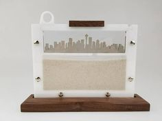 Own a custom, urban ant farm! Walnut and laser-cut acrylic create an ant farm under an urban landscape of your choice. Secured with Post screws and snap-fit top for easy maintenance and cleaning. 8.5w x 6.25h upright farm mounted in a 10w x 2.25d x .75h polished walnut base. Sand and ants not included (But links to suppliers provided)
