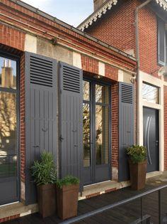 Porte fenêtre aluminium avec traverse haute, Gamme Tentation, coloris gris anthracite 7016. Terrasse en bois foncé pour cette maison en briques rouges. #fenêtre #aluminium #volet #rénovation #sur-mesure
