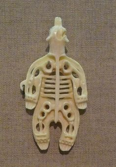 small sculpture of a shaman, mid-transformation into a bear. It's a few inches long, the kind of thing you might keep in your pocket.  Apparently an aspect of Inuit and Eskimo shamanism is not only the shaman's ability to transform into a bear (or vice versa), but also his ability to contemplate or see his own skeleton. So these three symbols of bear, shaman and skeleton together symbolize the underlying power of the shaman in much of the far north and the arctic.