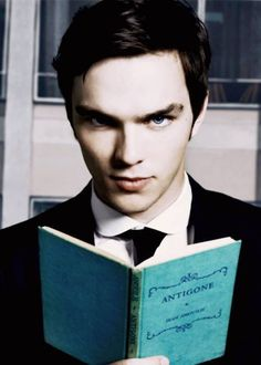 A pretty guy in a suit and tie reading... be still my heart