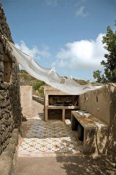 La cucine all'aperto, riparata da una garza di lino bianco. Il pavimento è decorato da piastrelle ottocentesche recuperate con il restauro del dammuso