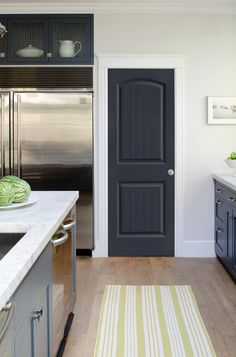 Modern monochromatic kitchen featuring marble countertops, stainless steel fridge, paneled cabinet doors and a Select™ Series Cheyenne® style, grey, pantry door