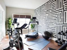 Stunning home gym and yoga room boasts a black and white graphic hand painted wall alongside NordicTrack gym equipment and yoga mats atop a wood like floor.