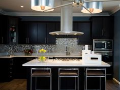 brushed aluminum chandelier, Silestone countertops made with crushed pieces of mirror in it, a central brushed aluminum exhaust hood and a glamourous mosaic tile silver backsplash
