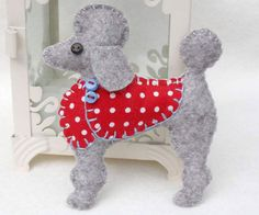 Handmade felt dog ornament for Christmas or any occasion. Mimi is a Poodle made from light grey felt, with a jolly buttoned jacket in red dotty fabric, and a cotton loop for hanging. She measures 3.5