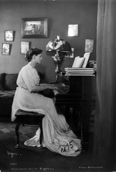 """Ethel Barrymore, in long dress, playing the piano (c.1903). Photograph by Joseph Byron. Library of Congress, Prints and Photographs Division. Barrymore (1879-1959) was regarded as the """"First Lady of the American Theater."""" Her first appearance on Broadway was in 1895, in a play called The Imprudent Young Couple which starred her uncle John Drew, Jr., and Maude Adams. She appeared with Drew and Adams again in 1896 in Rosemary."""