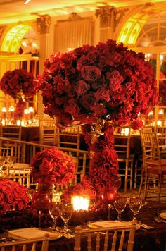 Fresh red roses wrap around this over the top floral arrangement for an utterly elegant look. #WeddingCenterpieces