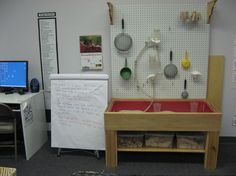 Peg board above sensory table.
