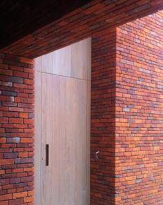 Huis in Heffen - detail ; houten strook loopt helemaal door tot boven in het lage volume. Hierin zit de deur