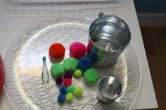 Opposites learning activity: big vs. small. Using a tweezer for fine motor practice to put the big poms in the big bucket and the little ones in the little bucket.