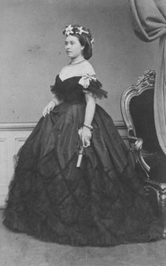 Crown Princess Victoria of Prussia, later German Empress Frederick, in the 1860s. Evening wear- Deep flounces or tiers, off the shoulder neckline, double skirts, raising outer into puffs with a porte jupe/dress elevator and later in period, long gloves for evening.