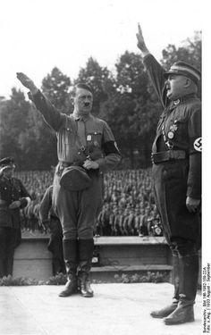 """Adolf Hitler y Ernst Röhm en Nürnberg, Alemania, Agosto de 1933. Ante el poder que estaban adquiriendo en las calles las SA de Ernst Röhm, Hitler ordenó una purga entre el 30 de Junio y el 2 de Julio de 1934 en la que fueron asesinados la mayoría de las SA, incluyendo a Röhm. Pasó a la historia como """"La noche de los cuchillos largos""""."""