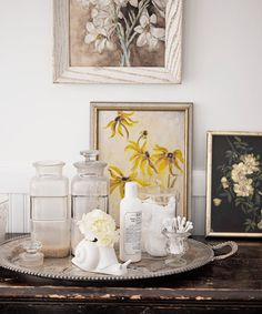 Flea-market paintings, along with vintage apothecary jars corralled on a silver tray, pretty up the guest bath.   - CountryLiving.com