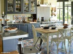 Une cuisine avec carreaux de ciment Ouverte sur le salon et sur le jardin, cette cuisine a le sens de la convivialité. Les meubles en bois massif faits sur mesure s'associent à des modèles créés en série, comme le bar. Pratique, celui-ci est recouvert de zinc.