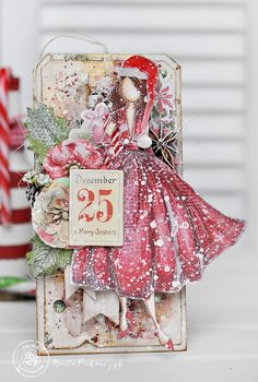 """I love the magic of Christmas time, and I love to create different decorations for each year. For this project, Julie Nutting's 'Rita' doll received a Christmas hat, and she is the focal decoration for my Christmas tag."" ~ Marta Piekarczyk"