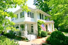 Gorgeous white southern exterior home with black shutters and door. Lush garden and very all American looking!