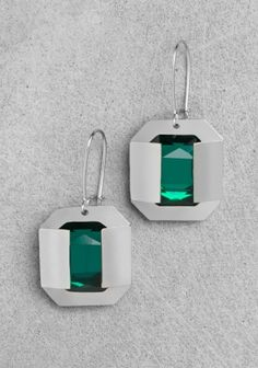 RHINESTONE EARRINGS  & Other Stories    DETAILS  MATERIALS & CARE  SHIPPING  & OTHER STORIES These pendant earrings consist of a large faceted rhinestone mounted onto a folded metal frame paired with a round rhinestone. Length: 4.5 cm.