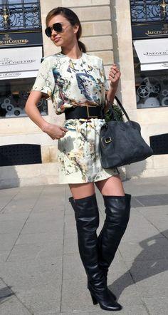 Stivali cuissard sopra il ginocchio color nero, opachi, abbinati ad un mini dress a manica corta, sfondo bianco con stampa colorata che ritrae simboli egizi. Nero anche il cinturone con fibbia dorata che porta in vita; la borsa, in pelle scamosciata color cobalto, riprende i colori della fantasia dell'abito. Molto sexy!