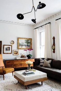 Neutral living room design featuring white walls and curtains, a dark gray contemporary sofa, a large off-white and gray patterned area rug, and antique art and furniture from the 19th-century to mid-century modern eras - Eclectic Home Decorating Ideas &