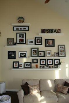Photo wall. I like the use of shelves.