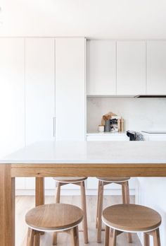 White on white kitchen peppered with wood details and decor.