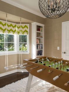 Super fun kids playroom.  Love the soft shag rug, vintage game, modern acrylic seat, playful chevron green blinds.