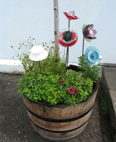 cute idea for flowers in the garden out of small cups along with a couple of saucers