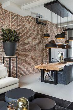 Liefhebbers van industriële interieurs kunnen hun hartje ophalen bij het zien van deze moderne zwarte keuken. Door de hanglampen op verschillende hoogtes te hangen creëer je een speels effect. De massiefhouten keukentafel met stalen onderstel en de steens #lightsforkitchen #industrialdesign