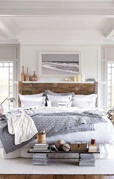 cama grande con ropa de cama revuelta, colcha fina y cojines en escalera en tonos blancos y grises