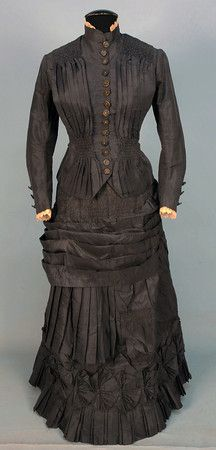 SILK TAFFETA BUSTLE DRESS, 1880's. 2-piece slate grey with peplum bodice having vertical pleats ruched at the shoulder and waist, skirt decorated with bands of ruching, pleats and a band of self pinwheels, lined in brown cotton. B-34, W-25, skirt L-40. (