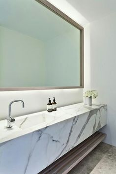 Incredible bathroom with Statuary Marble floating vanity with modern faucet and backlit vanity length mirror.