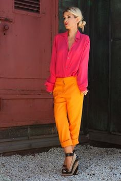 Hot pink long sleeve shirt with cuffs up, open convertible collar, neon gold skinny pants with rolled cuffs, black and tan espadrille wedges with peep toes and ankle straps, bun