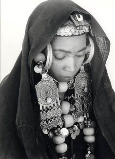 Black and white portrait of a Berber (Amazigh) woman, adorned in elaborate jewelry, from Morocco. Costume Ethnique, 3d Foto, Yoruba, We Are The World, Black And White Portraits, Tribal Jewelry, Tribal Clothing, African Jewelry, World Cultures