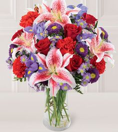 This beautiful bouquet will surely catch their eye with its stunning array of red roses, pink lilies, purple iris, purple aster and more.