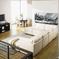 Minimalist Living Room Interior Design with White Wall Paint Color and Wooden Flooring and U Shaped White Leather Sofa Set feaet Rectangular Shaped White Carpet Area also Ottoman