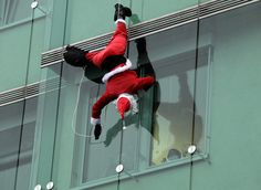 A member of Slovenia's special forces unit dressed in a Santa Claus outfit waves to a patient as he abseils from the roof of a paediatric clinic in Ljubljana