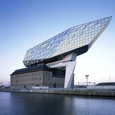 """There's a blinged-up new landmark on the Antwerp skyline: a disused fire station has been repurposed into a new port house for 500 staff by Zaha Hadid Architects, with a huge extension designed to """"float"""" above the original structure, reflecting the colours from sea and sky. Panoramic lifts provide access to the annexe, with an external bridge providing panoramic views of the city and the port. Another stunning example of architecture from the late great Zaha Hadid's practice. #architecture…"""