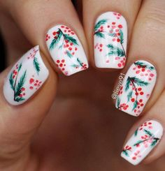 In the spirit of the upcoming holidaysc white manicure decorated with evergreen twigs and red berries.